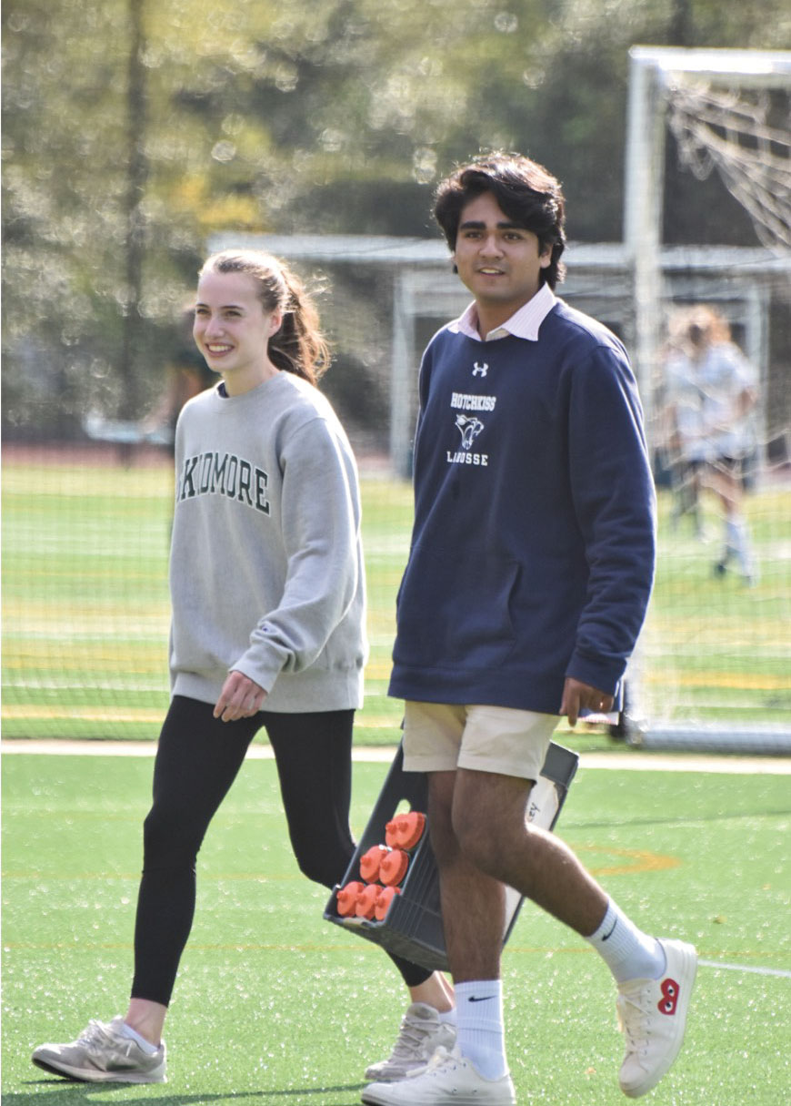 Axel Bhandari '19 carries water bottles onto the field alongside forward Maggie Hatch '21.