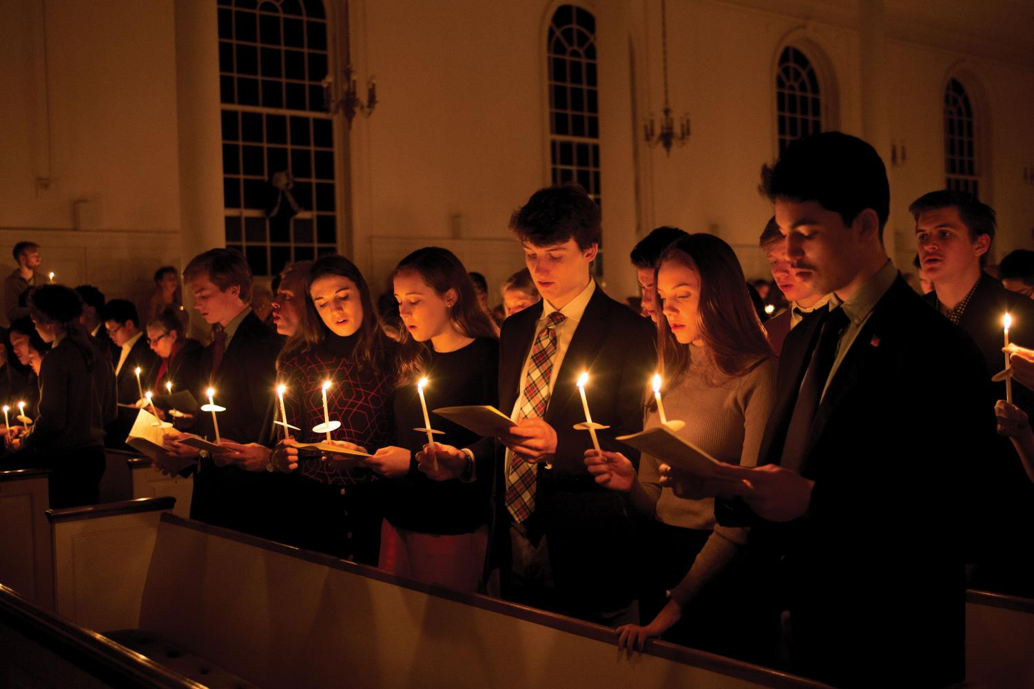 Students hold candles, each lit from a single flame, and sing holiday music at Lessons and Carols last Sunday.