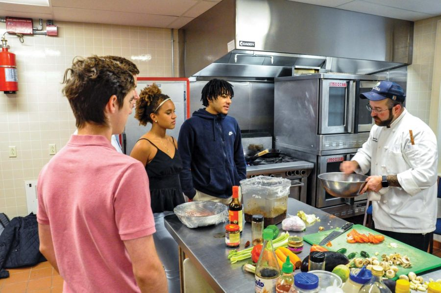 Members of the Chinese 350 class watch Michael Webster prepare to cook a wok dish.