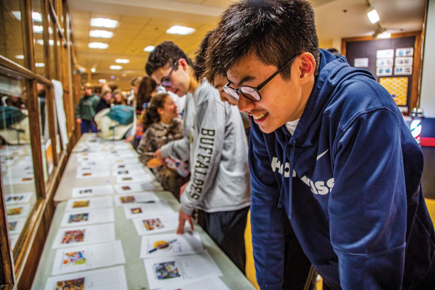 Ryan Tse '23 looks at the bidding sheets at the KF Faculty Dinner Auction last Wednesday.