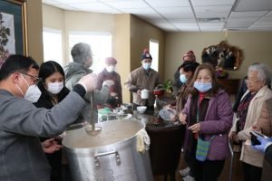 Ella Yu '24 (second to left) and her father (far left) work at a soup kitchen serving elderly citizens after a storm battered Texas and left millions without access to water and hot food.