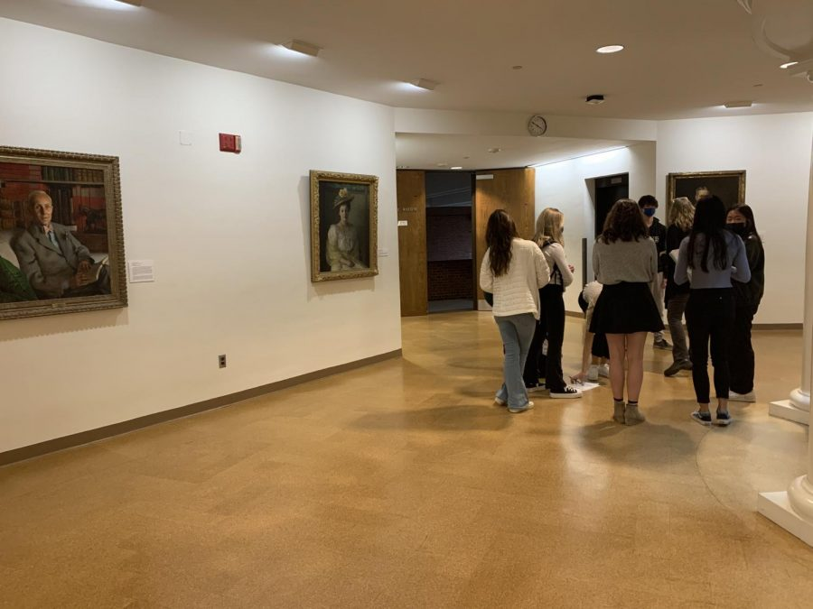 Students view the portrait exhibit with Ms. Terri Moore, instructor in art.