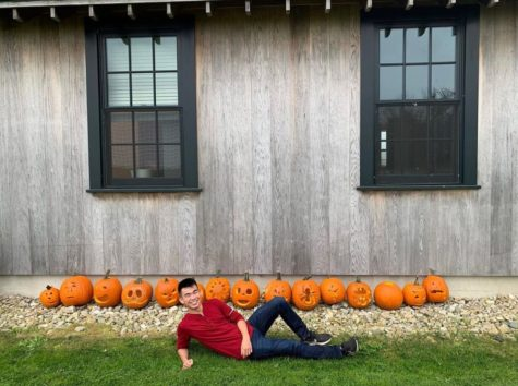 Cooper Roh 22 lies in front of pumpkins carved during the Farm Festival.